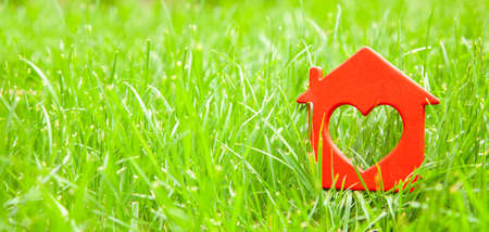 Sweet house in the grass. Concept of eco house, cottage. Symbol of  house with heart on green summer lawn. Copy space for text