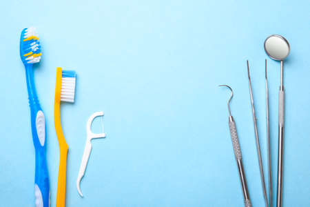 Dental instruments. Dental mirror, probe hook, tweezers and toothbrush with floss on blue background