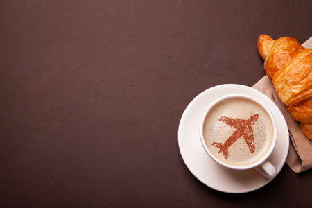 Mug of coffee with an airplane on the foam. Morning coffee with croissant in flight. Stock Photo