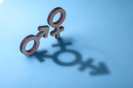 Symbols of man and woman cast shadow in the form of transgender on blue background