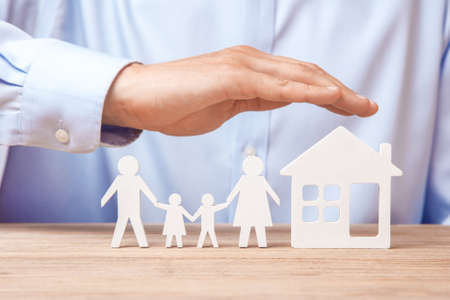 Family insurance and home. Man in  shirt covers his family with his father, mother, son and daughter and the house.