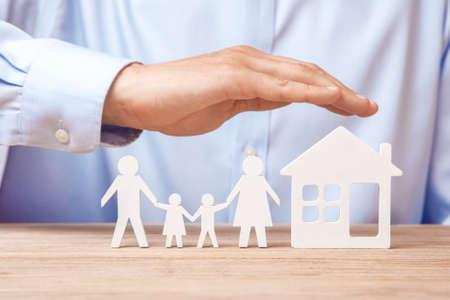 Seguro familiar y de hogar. El hombre en camisa cubre a su familia con su padre, madre, hijo e hija y la casa.