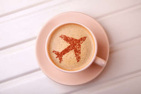 Cup of coffee with airplane on foam. Morning coffee in flight Stock Photo