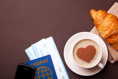 Ð¡up of coffee with heart on the foam. I like to break coffee with  croissant in flight. Paspor and ticket with smrtrfonom and cup of coffee Archivio Fotografico - 106426329