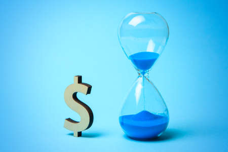 Hourglass and symbol of money dollars on blue background. Time is money
