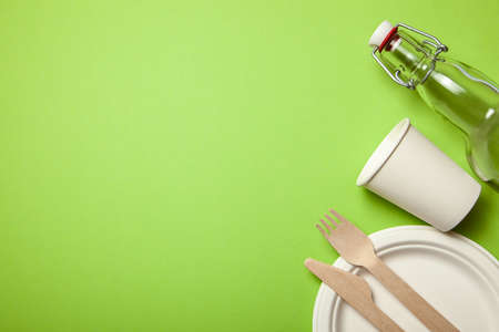 Eco-friendly disposable utensils made of bamboo wood and paper on a green background. Draped spoons, fork, knives, bamboo bowls with paper cups and glass bottle