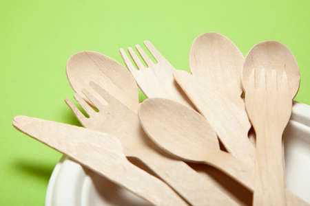 Eco-friendly disposable utensils made of bamboo wood and paper on a green background. Draped spoons, fork, knives, bamboo bowls