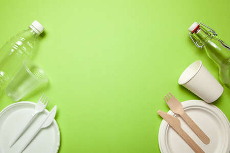 Plastic and Eco-friendly disposable utensils made of bamboo wood and paper on a green background. fork, knives, plates, cups and bottle