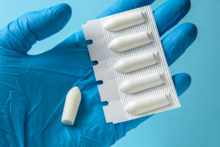Suppository for anal or vaginal use in the hands of doctor in gloves. Candles for treatment of hemorrhoids, temperature, thrush, inflammation