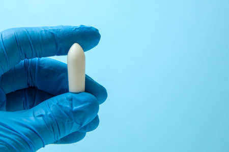 Suppository for anal or vaginal use in the hands of doctor in gloves. Candles for treatment of hemorrhoids, temperature, thrush, inflammation. Copy space for text