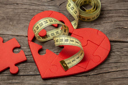 Red heart puzzle and yellow measuring tape. Overweight kills the heart. Concept Obesity Stock Photo