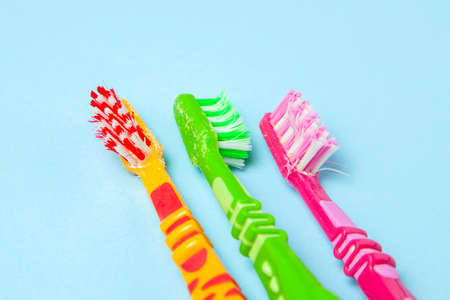 Used dirty toothbrushes on blue background. How to choose toothbrush