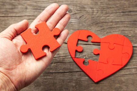 Man holds in his hand part of the puzzle from the heart. How to find your soul mate or work for the soul. Stockfoto