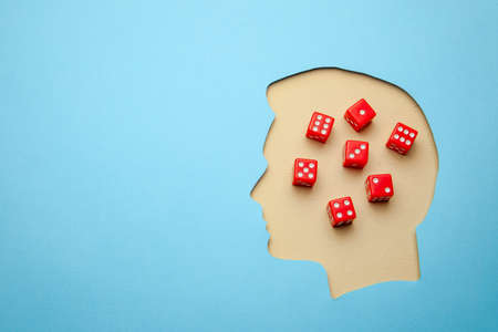 Game addiction or addict. Human head profile with gaming dice. Copy space for text Reklamní fotografie