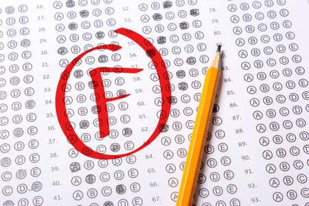 Zła ocena F jest pisana czerwonym długopisem na testach