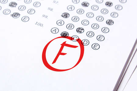 Bad grade F is written with red pen on the tests. Stock Photo