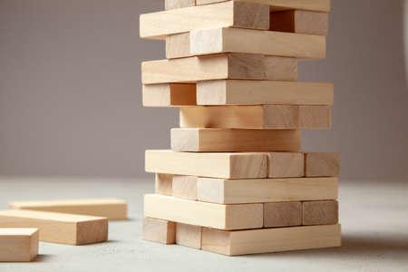 Tour de blocs de bois sur fond gris. Jeu de société pour toute la famille ou la fête. Concept de construction d'entreprise ou d'équipe de construction.