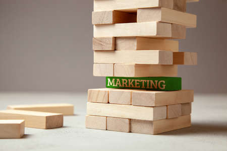 Good marketing is the basis of successful company. The tower of wooden beams and one block green with the inscription Mrketing