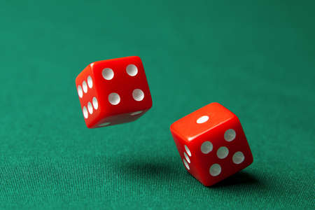 Two red dice on green poker gaming table in casino. Concept online gambling Stock Photo