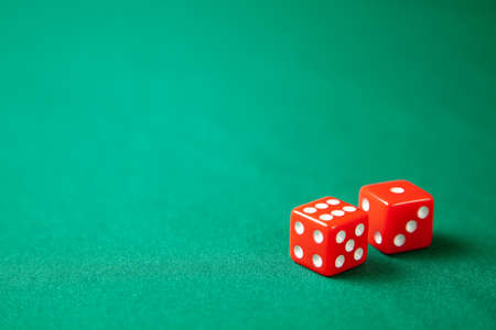 Two red dice on green poker gaming table in casino. Concept online gambling. Copy space for text Stock Photo