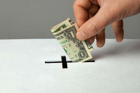 L'homme met le don dans sa main avec le dollar dans la fente sous forme de croix chrétienne Banque d'images