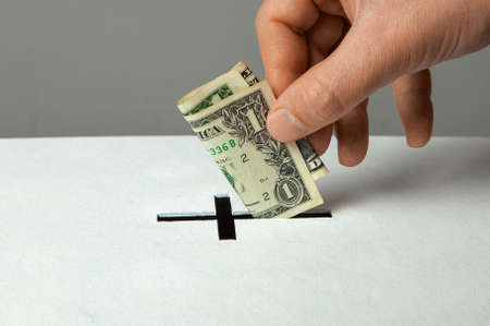 Man puts donation in his hand with dollar in slot in the form of Christian cross Stock Photo
