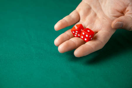Man holds two red dices and throws them on green poker gaming table in casino. Concept of online gambling, winner or player. Copy space for text