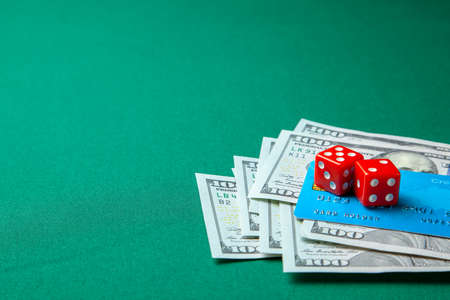 Gambling in casino. Money cash dollars and credit brief with dice for games on the green table. Stock Photo