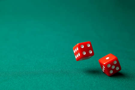 Two red dice on green poker gaming table in casino. Concept online gambling. Copy space for text.