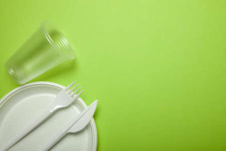 Plastic disposable utensils on green background. fork, knives, plates, cups. Stock Photo