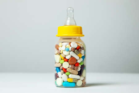 Baby feeding bottle filled with pills. With mothers milk, the child gets everything the mother eats. closeup Stock Photo