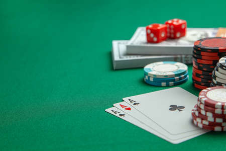 Concept of gambling in casino, sports poker. Playing cards with dice and colored chips with cash money dollars on green gaming table. Copy space for text