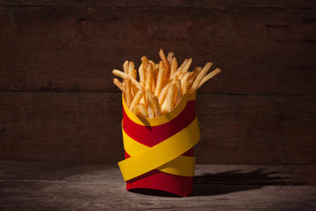French fries in a red packing box on wooden table with yellow police ribbons