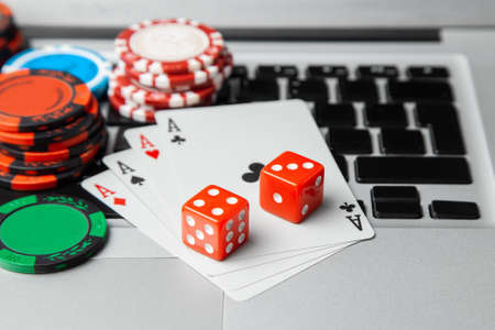 Online casino laptop. Laptop keyboard and chips with dice and playing cards on a green gaming table. Game addiction gambling. Poker online.
