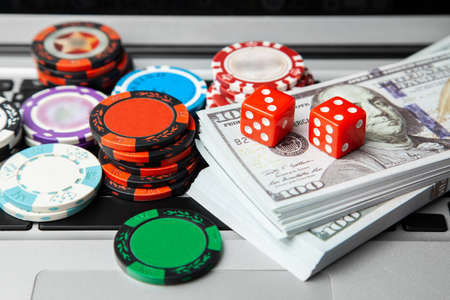 Online casino laptop. Laptop keyboard and chips with dice and money cash dollars on green gaming table. Game addiction gambling. Poker online. Stok Fotoğraf