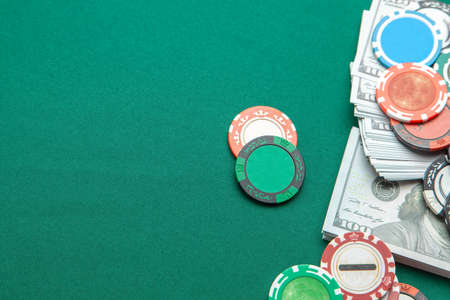 Concept of gambling in casino, sports poker. Gaming colored chips with cash cash dollars on green gaming table. Copy space for text Standard-Bild