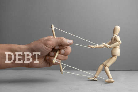 Debt holds back and directs us like puppeteer doll. The hand of the puppeteer is holding scared wooden doll.