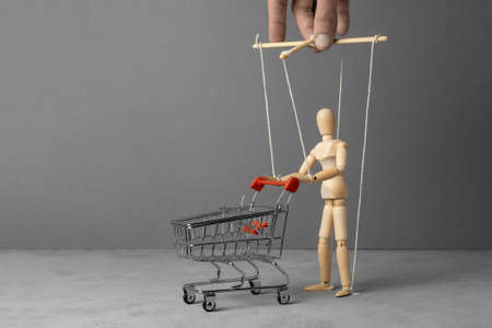 Control over the behavior of the buyer. Man with a shopping trolley from the supermarket like doll led by puppeteer. Copy space for text