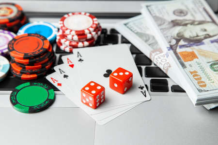 Online casino laptop. Laptop keyboard and chips with dice and playing cards and money cash dollars on green gaming table. Game addiction gambling. Poker online. Stok Fotoğraf
