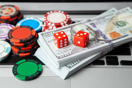 Online casino laptop. Laptop keyboard and chips with dice and money cash dollars on green gaming table. Game addiction gambling. Poker online. Stock Photo