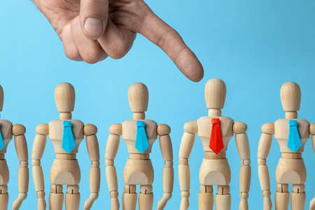 Staff recruitment. Choosing a leader for a business team. The employer giver points his finger at the worker in the red tie.