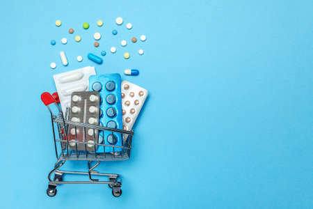 Shopping basket and pills in blisters. The concept of buying drugs online, delivery of medical devices. Copy space for text Foto de archivo