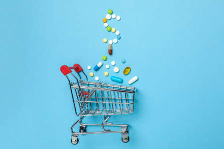Shopping basket and pills in form of dollar. The concept of buying drugs online, delivery of medical devices.