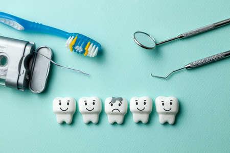 I denti bianchi sani stanno sorridendo e il dente con la carie è triste su sfondo verde menta. Spazzolino da denti filo interdentale e strumenti del dentista specchio, gancio