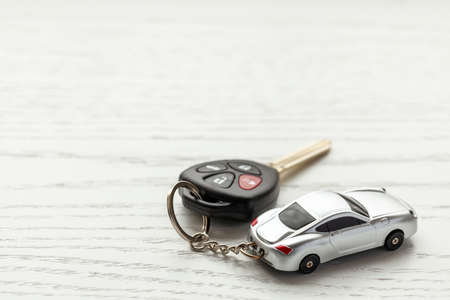 Car keys with remote control security and car key chain on white wooden background. Copy space for text.