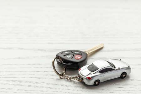 Clés de voiture avec télécommande de sécurité et porte-clés de voiture sur fond de bois blanc. Copiez l'espace pour le texte.