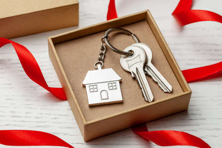 Keychain house and keys with red ribbon and gift box on white wooden background