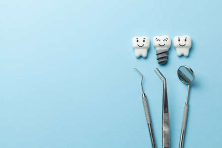 Healthy white teeth and implants are smiling on blue background and dentist tools mirror, hook. Copy space for text