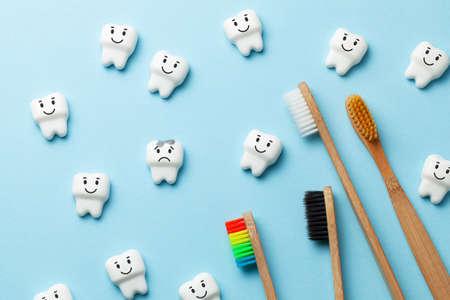 Gesunde weiße Zähne lächeln und Zahn mit Karies ist auf blauem Hintergrund und Zahnbürste traurig