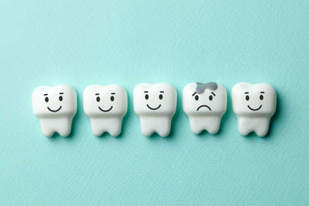 Healthy white teeth are smiling and tooth with caries is sad on green mint background